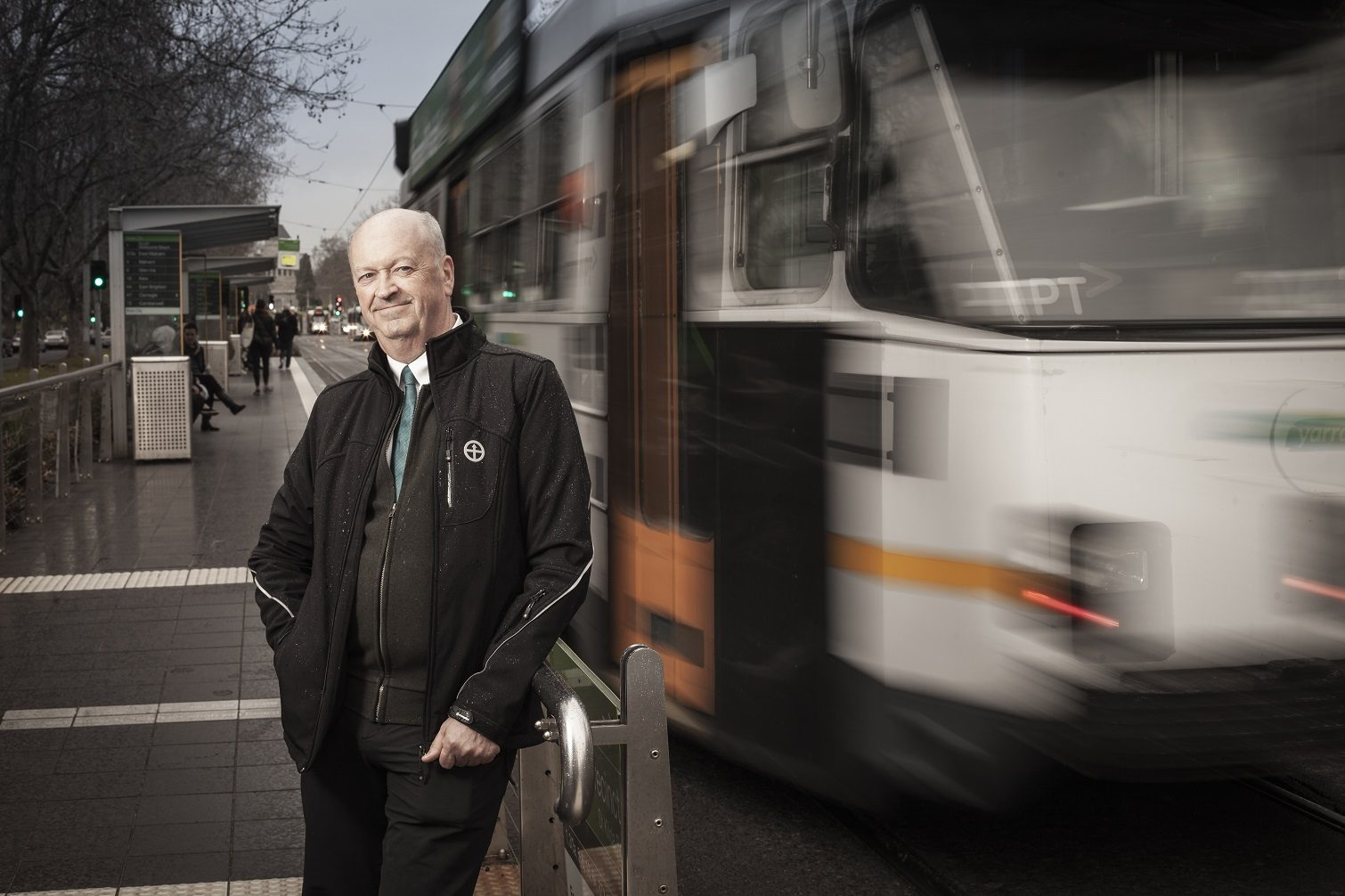 Graham Currie stands at a Melbourne tram stop while a tram goes by.