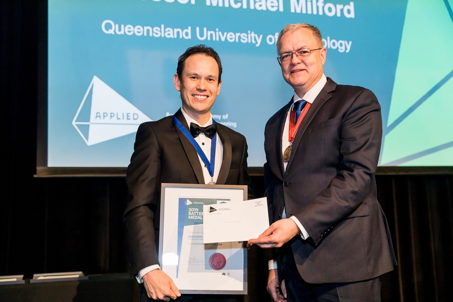 Michael Milford accepts his award from Iven Mareels