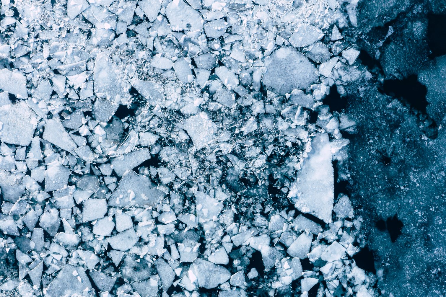 Glacier Lagoon with icebergs from above. Aerial View. Cracked Ice from drone view.